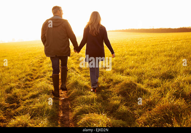Couple Walking in a Field Holding Hands - Stock Image