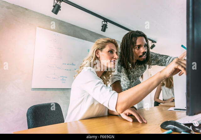 Designers working on a project and discussing new ideas - Stock Image