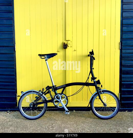 A black Brompton bicycle propped against a yellow painted beach hut door. - Stock Image