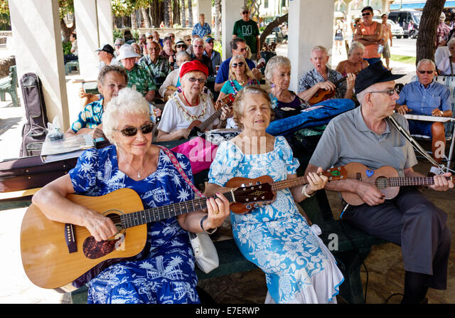 Waikiki Beach Honolulu Hawaii Hawaiian Oahu Kuhio Beach Park free ukulele lessons senior man woman playing music - Stock Image