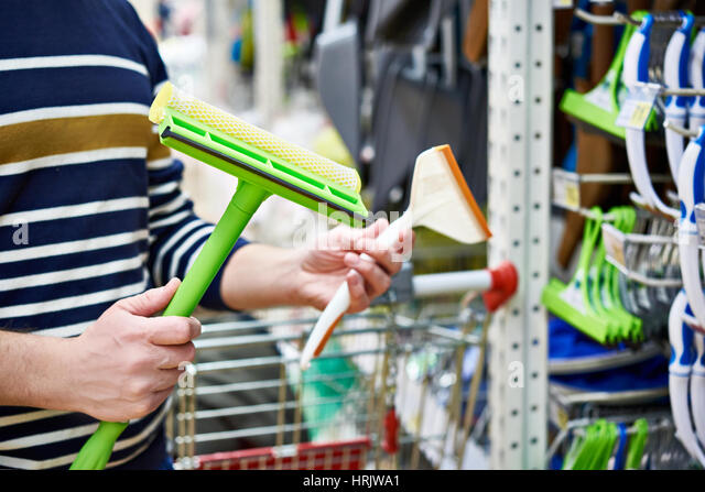 Man chooses brushes and scrapers for cleaning the car in shop - Stock Image