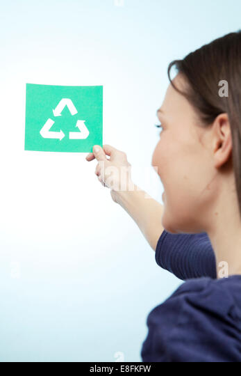 Woman holding paper cut out of recycling symbol - Stock Image