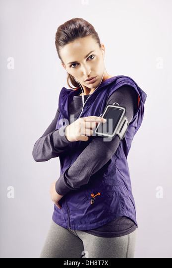 Fitness woman wearing earphones and mp3 player. Female runner listening music on grey background - Stock Image