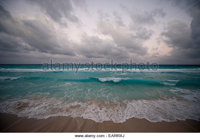 Waves crash onto the shore in Cancun, Mexico. - Stock Image