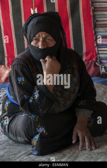 Bedouin grandmother seated on the dirt of her tent outside Amman, Jordan - Stock Image