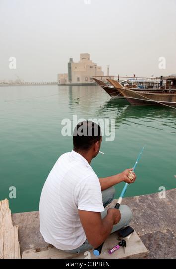 Man fishing with modern Museum of Islamic Art to rear in Doha Qatar - Stock Image