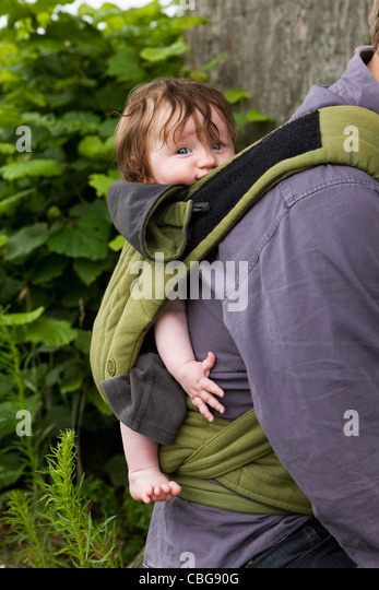 A father carrying his baby daughter in baby carrier, focus on baby - Stock Image