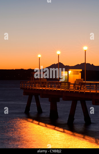 Silhouetted pier with people fishing off dock at sunset on Puget Sound with Olympic mountains Edmonds Washington - Stock-Bilder