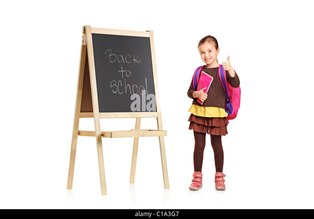 A child next to a school board holding book and showing thumb up - Stock Image
