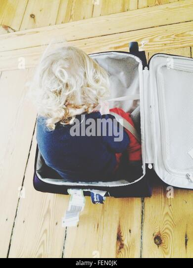 Rear View Of Girl In Suitcase At Home - Stock-Bilder