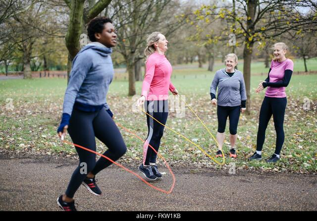 Women and teenager competing with skipping rope in park - Stock Image