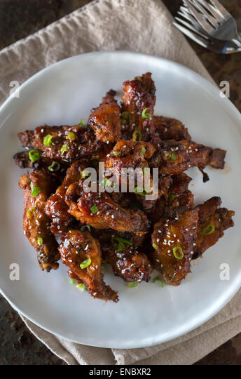 Asian-Style Sticky Chicken Wings sprinkled with sesame seeds and scallions served on a white plate. - Stock Image
