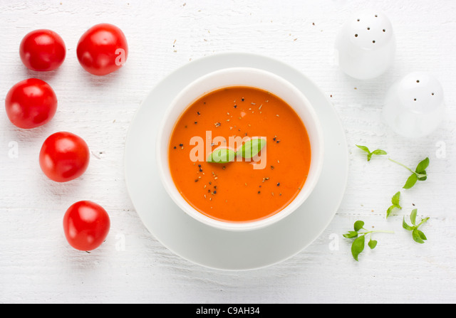 Tomato soup in white bowl surrounded with tomato's basil salt and  pepper shaker image shot from above - Stock-Bilder