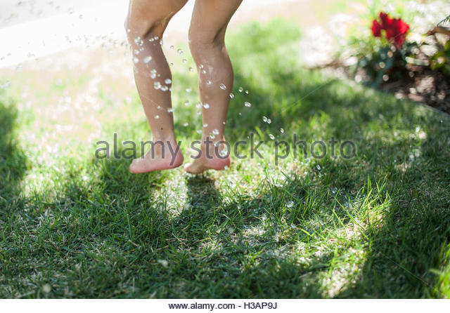 little girl's feet and legs jumping in the grass by the sprinkler - Stock Image