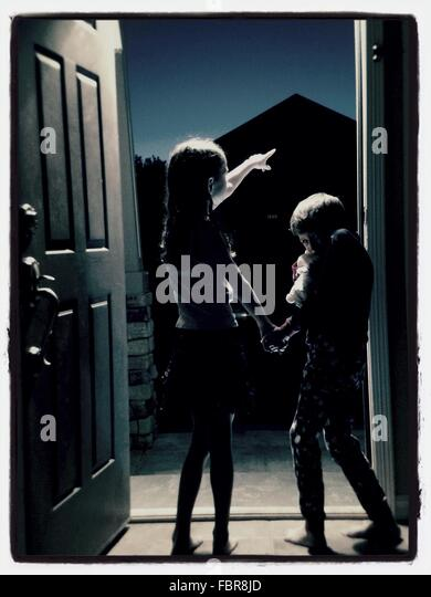 Siblings Standing On Door At Night - Stock Image
