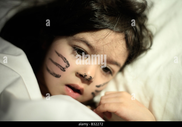 Five year old girl awakes with previous day s face paint She played a cat in a school production and didn t want - Stock Image