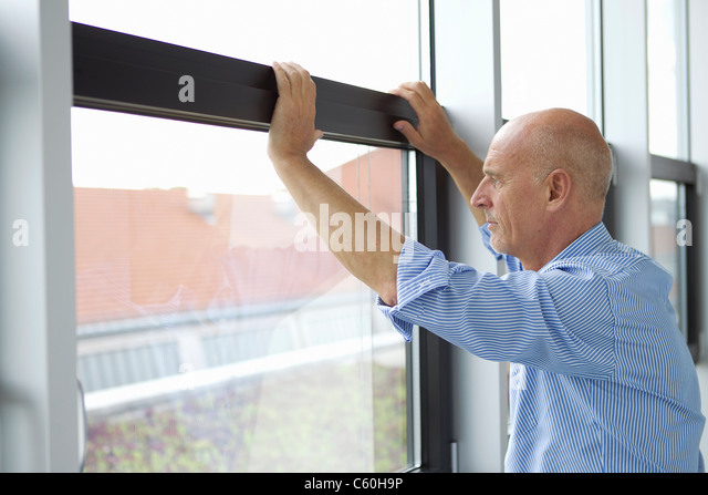 Businessman looking out office window - Stock Image