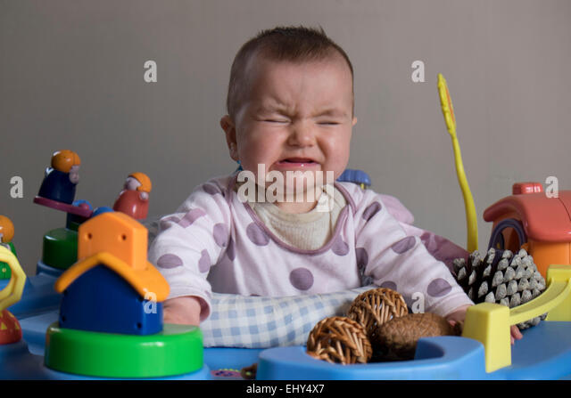 8 month old baby girl, in baby bouncer crying - Stock Image