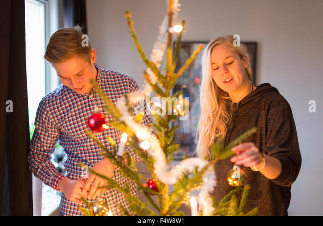 Couple decorating Christmas tree - Stock Image