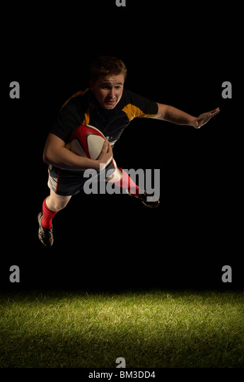 Rugby player mid air with ball - Stock Image