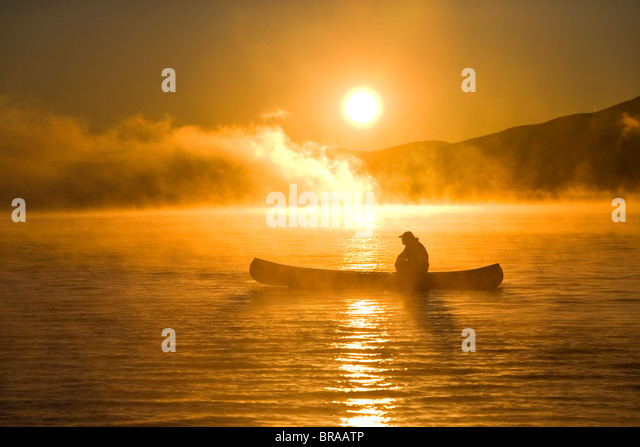 Canoeing in Lily Bay iin the mist at sunrise, Moosehead Lake, Maine, USA.  model released - Stock Image