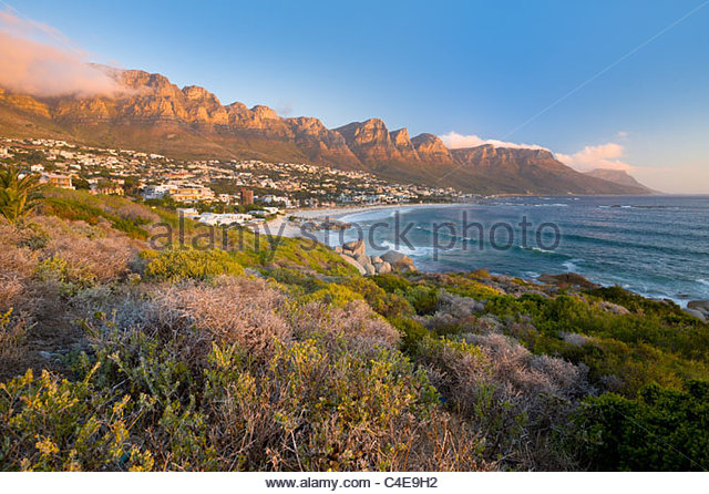 The Twelve Apostles loom over Camps Bay - Stock Image