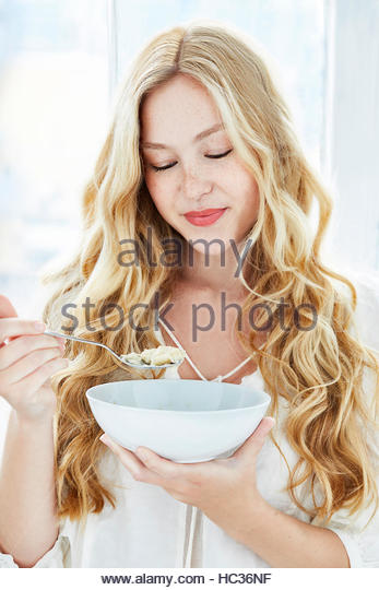 Portrait of young woman eating breakfast. - Stock Image