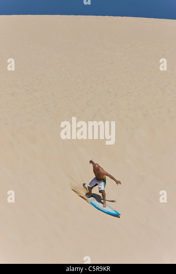 A surfer surfing a huge sand dune. - Stock Image