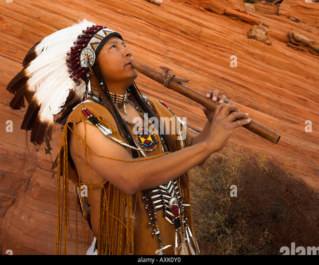 Native American Indian man person with cultural outfit uniform headdress feathers playing music instrument horn - Stock Image
