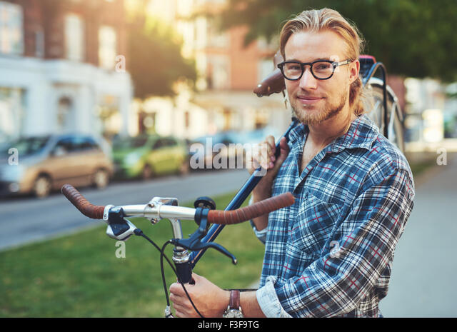 Portrait of blonde white man in the city with a bike - Stock Image