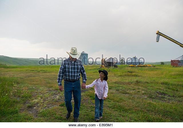 Grandfather and granddaughter walking on farm - Stock Image