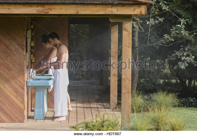 Young couple brushing their teeth at outdoor sink. - Stock Image