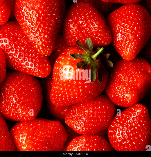FRESH STRAWBERRIES CLOSE UP WITH ONE 'HERO' STRAWBERRY IN THE CENTRE OF THE SHOT - Stock Image