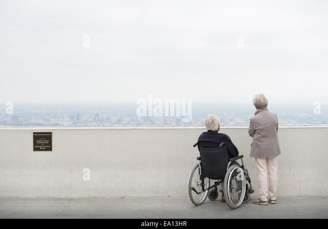 Rear view of senior man in wheelchair and his wife looking at city from viewing balcony Observatory Griffith Park - Stock Image