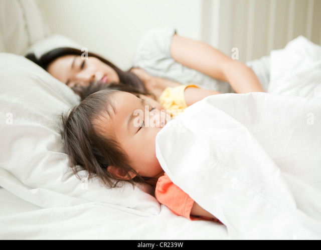 Mother with daughters (2-3, 4-5) sleeping together - Stock-Bilder