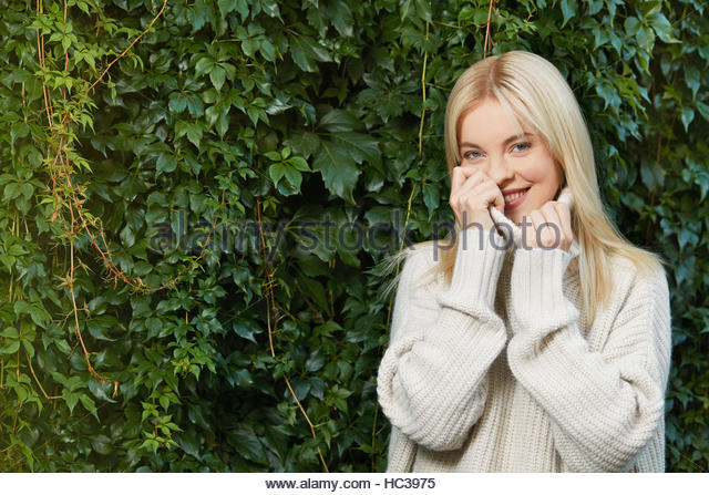 Young woman wearing sweater in front of hedge. - Stock-Bilder