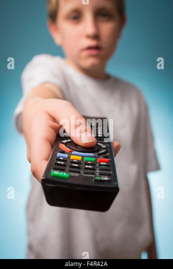 A bored boy changing channels using a TV remote control - Stock Image