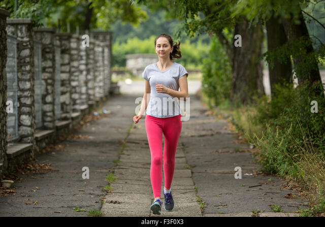 Young sports girl during a jog in the Park. Running, healthy lifestyle. - Stock-Bilder
