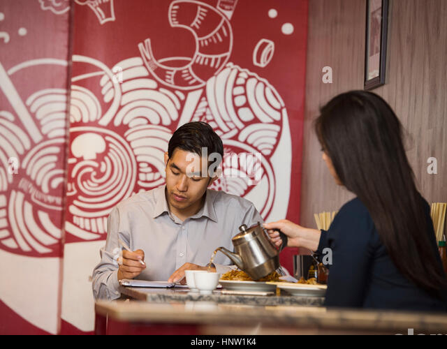 Chinese woman pouring tea in restaurant - Stock-Bilder
