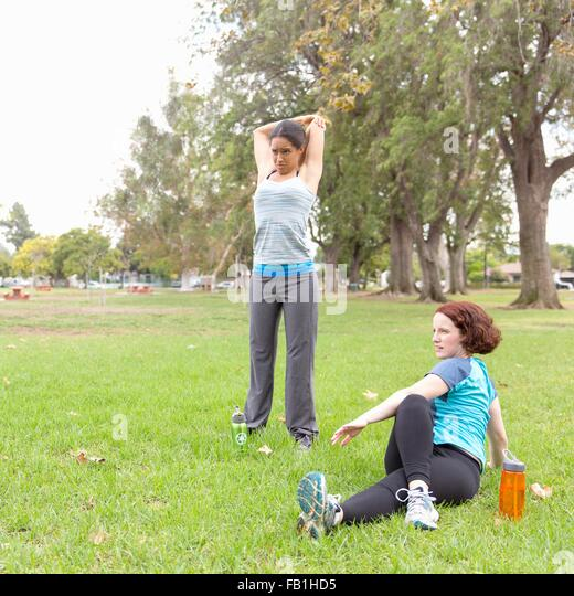 Young women wearing sports clothing on grass stretching - Stock Image