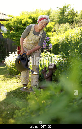 Image of healthy senior woman watering plants with a can in backyard garden. - Stock Image