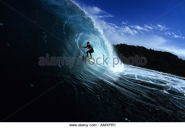 A surfer pulls into the barrel of a wave on the central Coast of NSW Australia - Stock Image