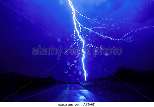 Drivers point of view of driving into  a  thunderstorm at night with a big huge lighting   bolt striking down the - Stock Image