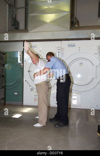 Sergeant pat searching inmate working in laundry. American maximum security prison. - Stock Image