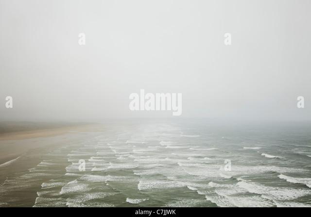 Waves crashing on foggy beach - Stock-Bilder