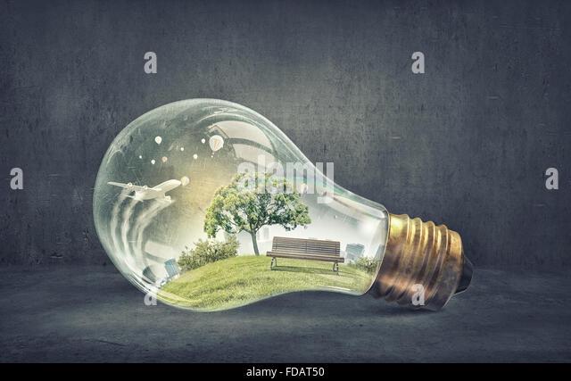 Eco life and energy saving concept in glass light bulb - Stock Image