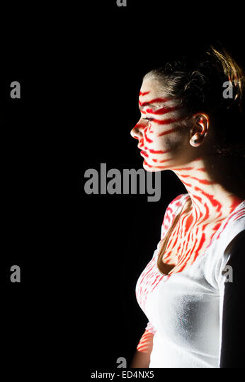 Digital Art: a young woman girl in profile with digital fingerprint image pattern projected onto her face. - Stock Image