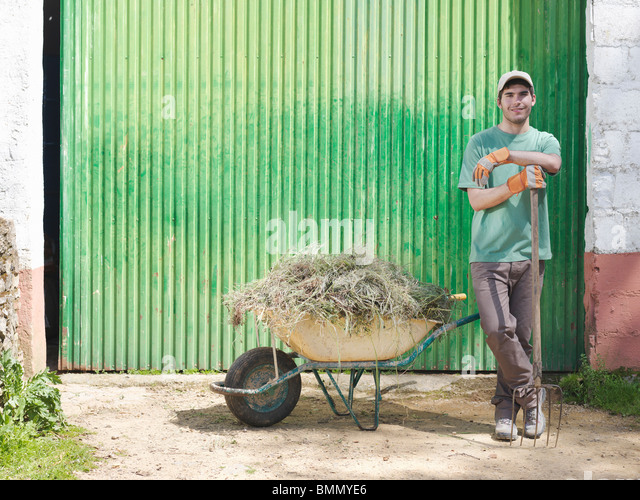 Man with wheelbarrow full of hay - Stock Image