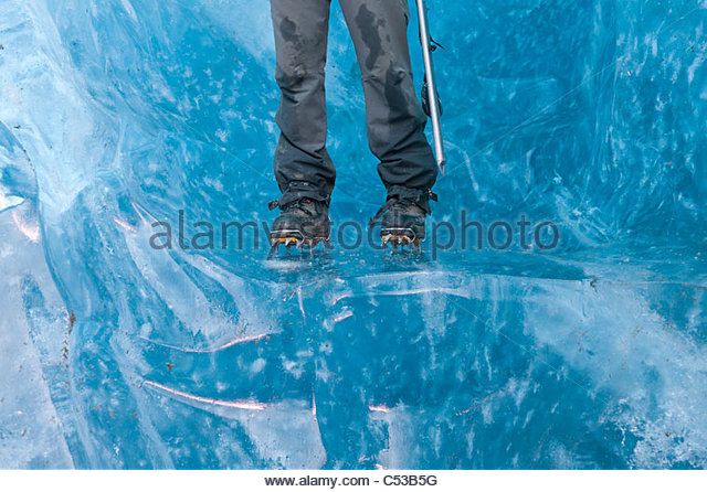 Man wearing crampons and standing on thick blue ice while hiking on Root Glacier in Wrangell-Saint Elias National - Stock Image