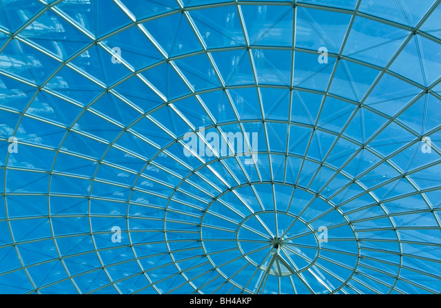 Bright blue sky seen through a modern architecture round or spiral window. - Stock Image